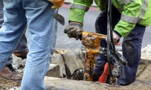 workmen digging a hole in the road