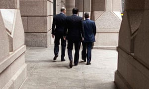 Three businessmen walk along a promenade on Wall Street in the financial district of New York