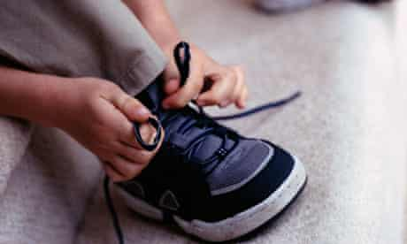 A boy tying his shoelaces