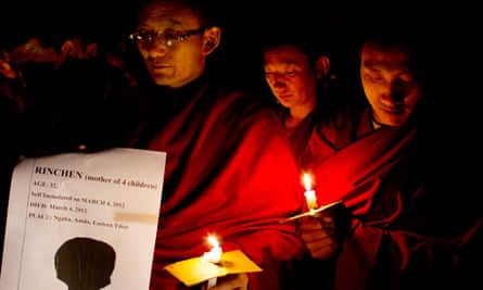 Exiled Tibetan Buddhist monks in a candlelit vigil to mourn the death the two women