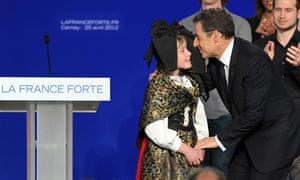 Nicolas Sarkozy kisses a girl dressed in traditional Alsatian costume at an election rally in Cernay