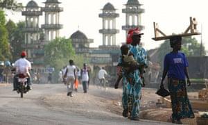 People walk along a road in Makeni, Sierra Leone