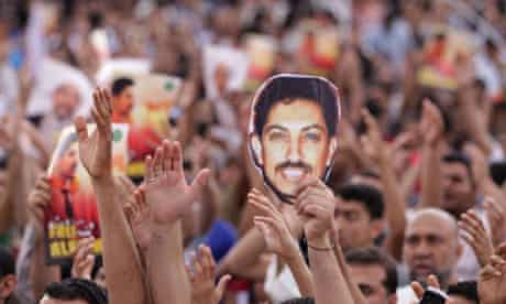 Bahraini anti-government protesters raise images of human rights activist Abdulhadi al-Khawaja
