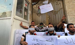 Palestinian men sit at the Red Cross HQ in Gaza show solidarity with the hunger strikers.