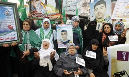 Palestinian women hold pictures of imprisoned relatives at a protest in Gaza City.