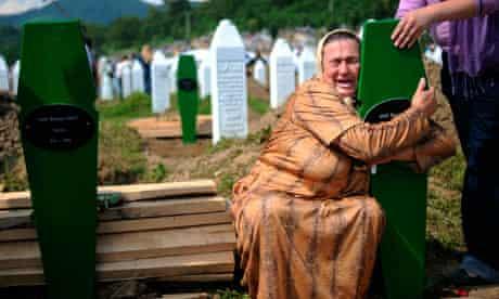 A Bosnian woman cries over newly dug gra
