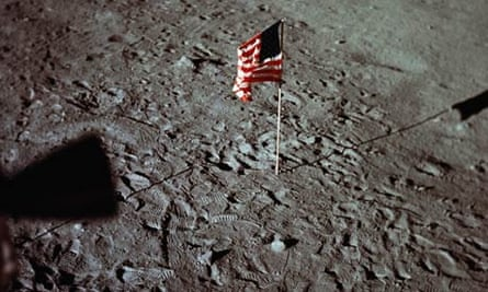 A US flag is surrounded by astronauts' footprints on the surface of the moon