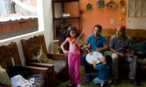 A young girl practises violin at home in a slum area of Caracas.