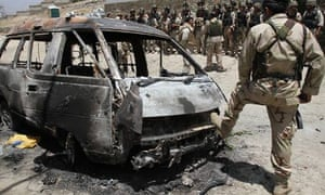 Afghan special forces guard the burnt-out vehicle used by Taliban fighters who attacked Qargha Lake