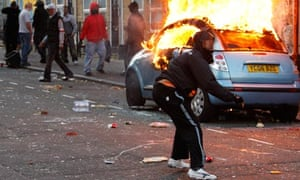 A rioter throws a rock at riot police in Hackney