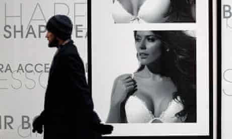 A man passes a La Senza lingerie advertisement