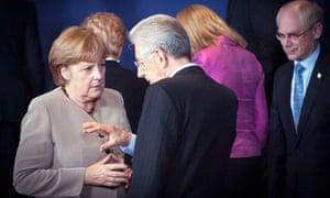 German chancellor Angela Merkel talks with Italy's prime minister Mario Monti at the EU summit