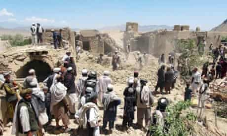 Afghan villagers gather at a house destroyed in a Nato raid in Logar province.