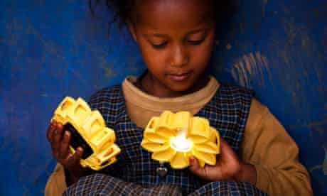 Girl holding two Little Sun lamps