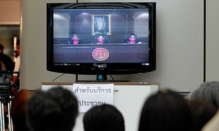 People watch on TV as the Thai constitutional court gives its verdict.