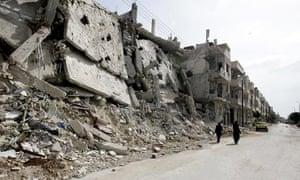Syrian women walk past destruction in the Bab Amro