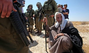 Israeli soldiers and settlers surround an elderly Palestinian man