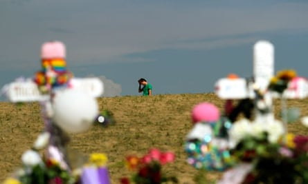 A mourner pauses near the memorial created for the Colorado massacre victims