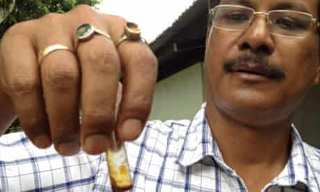Dr Anuj Baruah holds vial of bhut jolokia oil
