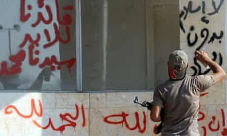 a man sprays an Arabic slogan - No Islam without Jihad - on a wall