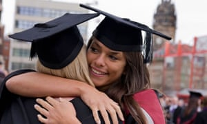 a young woman on graduation day hugging her fellow graduate. Image shot 2009. Exact date unknown.