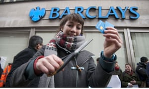 A customer cuts up her bank card outside a London branch of Barclays
