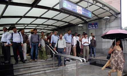 Commuters in Delhi exit a metro station