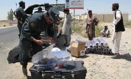 Afghan police inspect vehicles at a checkpoint in Qirshke.