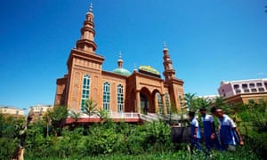 Chinese students walk by a mosque in Hami