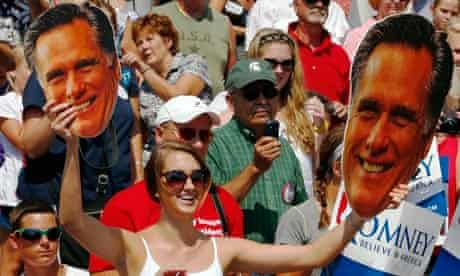 A supporter holds large cutout faces of Mitt Romney at a rally in Michigan earlier this month.