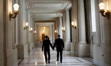 Same-sex couple Hata and Cadena walk a hallway after their wedding ceremony in San Francisco