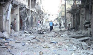People look at damaged buildings at Al-Zabadani