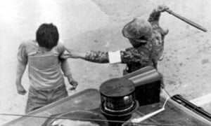 A paratrooper clubs a man arrested during anti-government demonstrations in Gwangju on 20 May 1980.