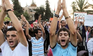 Anti-government protesters shout slogans during a demonstration in Amman