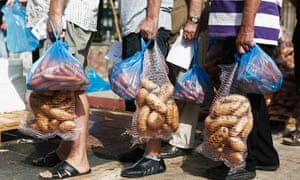 People hold sacks of potatoes during a food distribution organised by Golden Dawn, in Athens.