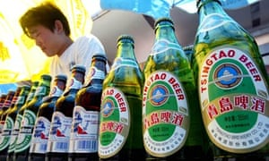A Chinese vendor waits for customers behind bottles of local and foreign beers