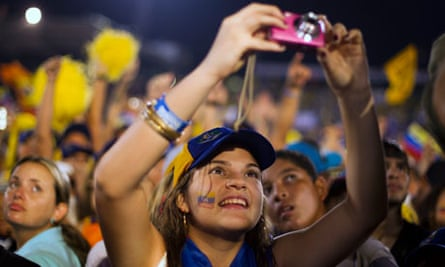 A supporter of Venezuela's opposition presidential candidate Henrique Capriles photographs him