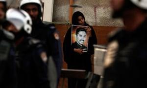 Demonstrator holds poster of Abdulhadi al-Khawa