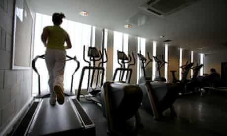 Woman runs on treadmill at gym