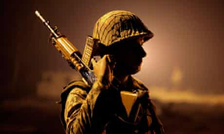 An Indian soldier stands guard on his side of the Line of Control near Jammu, Kashmir.
