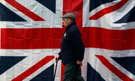 A man walks past a union flag  in west Belfast