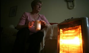 Pensioner keeps warm next to heater