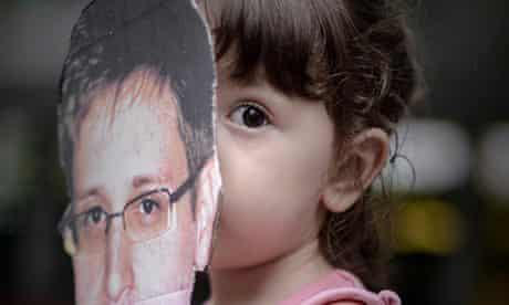 A child holds a cut out of Edward Snowden.