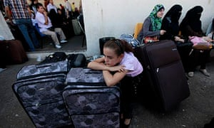 A girl rests on her luggage as she and her family wait to cross into Egypt at the Rafah crossing.