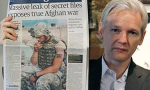 Secrets: Julian Assange holds up a copy of the Guardian reporting the release of the Afghan war logs