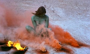 Judy Chicago's photograph Immolation IV: woman sitting in desert surrounded by burning smoke flares