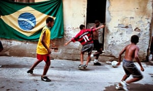 Young boys play football on the streets of a favela in Rio de Janeiro, Brazil.