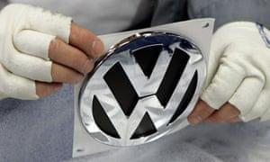 A factory worker holds a Volkswagen emblem