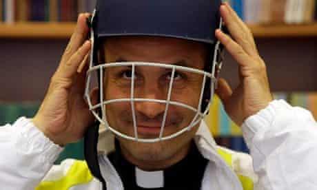 Monsignor Sanchez de Toca, puts on a cricket helmet after unveiling the Vatican team