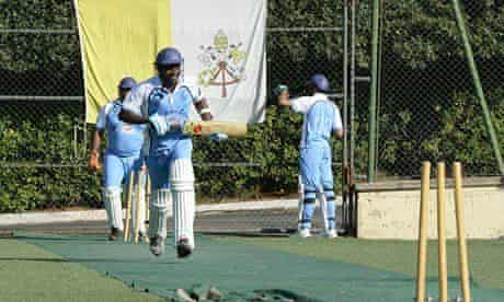Trainee priests play cricket at the Vatican, with the coat of arms of Saint Peter in the background.